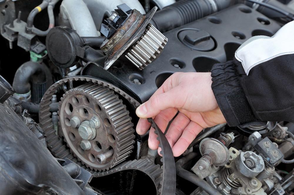 Car mechanic replacing timing belt at camshaft of modern engine